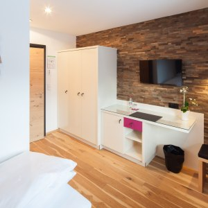 Einzelzimmer mit edler Steinwand.