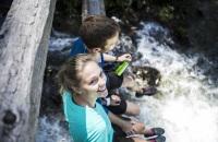 Glücklich in den Alpen unterwegs beim Wandern am Fluss