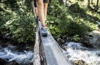 Schritt für Schritt über die Fluss- Brücke in den Bergen