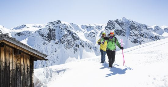 Mit den Skiern im Gepäck geht es auf den Gipfel