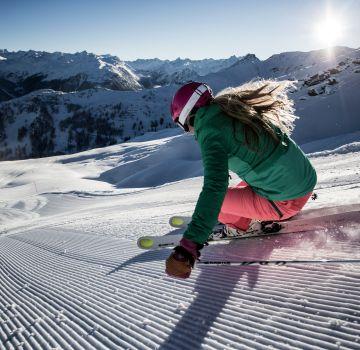 Mit Schuss den Berg hinunter fahren und den Winterurlaub genießen.