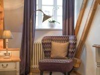 Farblich abgestimmte und edle Stoffe kombiniert mit Holz machen diese Zimmer zu etwas Besonderem