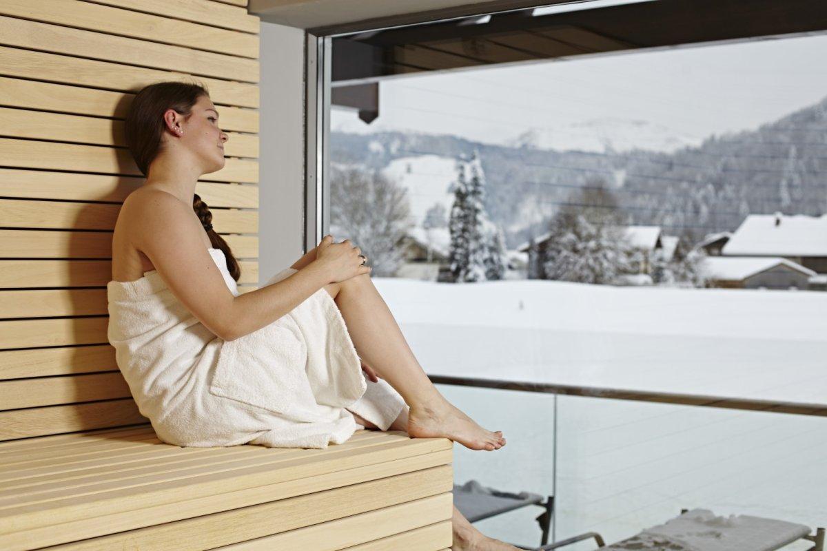Von der Sauna im Wellnesshotel Haubers aus hat man direkten Ausblick auf die Berge und den hauseigenen Natursee in Oberstaufen.