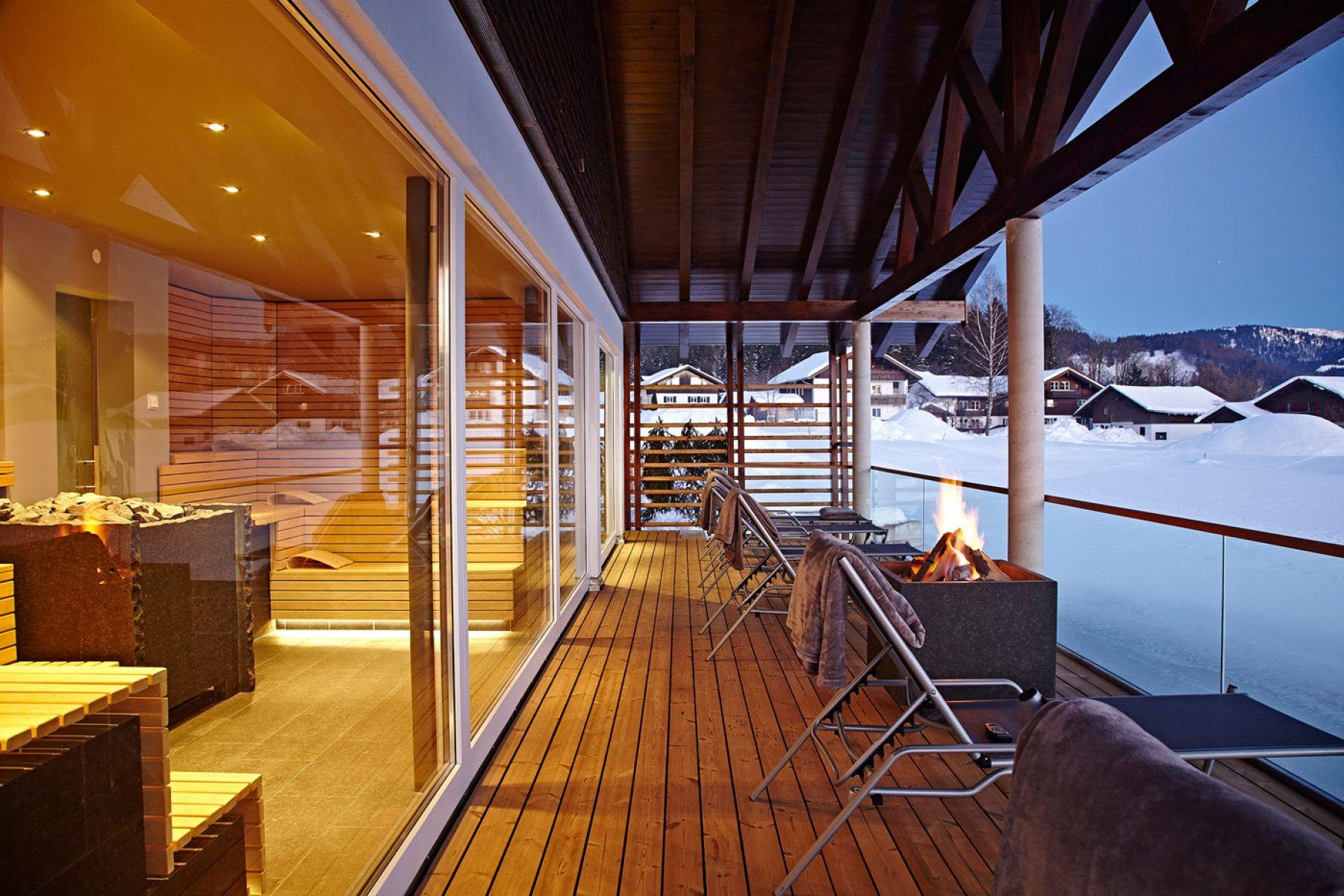 Wellness bei Kaminfeuer mit Ausblick auf den gefrorenen Natursee in Oberstaufen im Allgäu.
