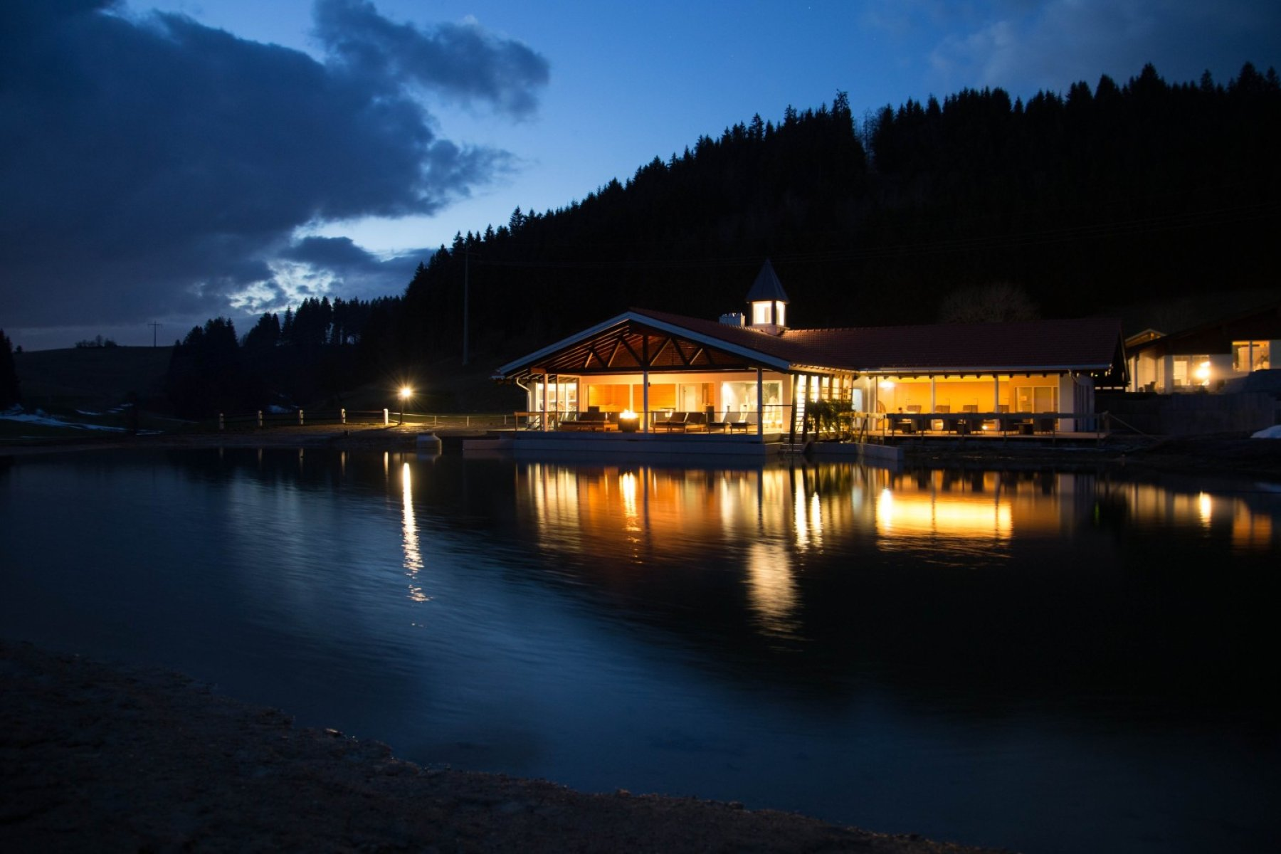 Haubers' Haus am See bei Nacht. Entspannte Wellnessstimmung direkt mit Blick auf den Natursee. Jetzt buchbar durch unsere Last-Minute Angebote.