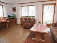 Wohnzimmer mit Couchgarnitur und Eßplatz