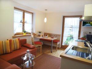 Wohnküche mit Couch und Eßplatz für 3 Personen mit direktem Zugang zum Südbalkon