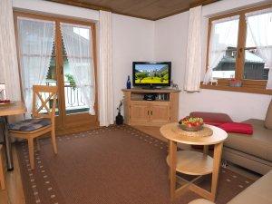 Wohnraum mit Couch und Eßplatz für bis zu 4 Personen und Zugang zum großzügigen Südbalkon