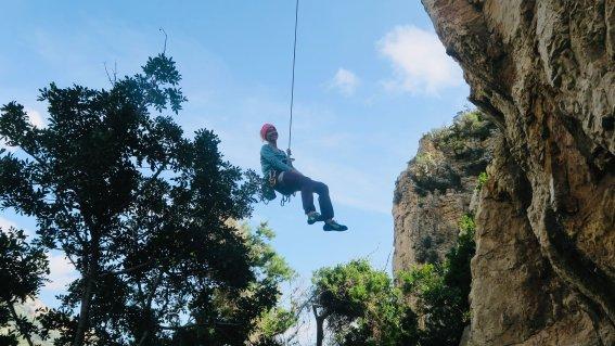 Kletterer beim Abseilen an einem Übungsfelsen