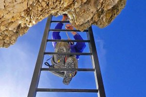Kletterer auf Leiter, Klettersteig, blauer Himmel