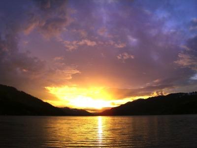 Die untergehende Sonne verwandelt den Alpsee in ein orange-rot leuchtendes Farbenmeer.