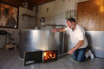 traditionelle Käseherstellung - Kupferkessel anfeuern