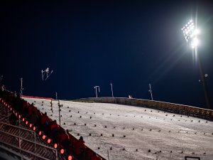 An athlete competes under the fllodlights in the Ski Jumping Women Large Hill Individual