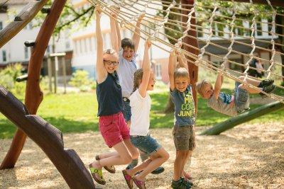Kinder hängen am Kletternetz