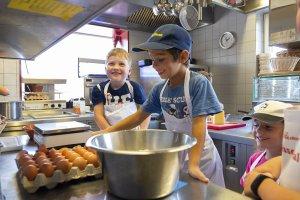Glückliche Kinderaugen beim Kässpatzen kochen