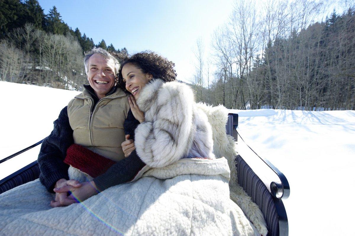 Wie in einem Wintermärchen fühlt man sich in warme Decken gehüllt oben auf dem Pferdeschlitten.