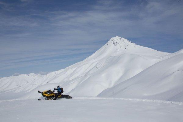 Schneemobilfahrer mit Vulkan