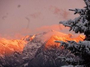 Ein grandioser Anblick - verschneite Berggipfel und orange-rotes Alpenglühen