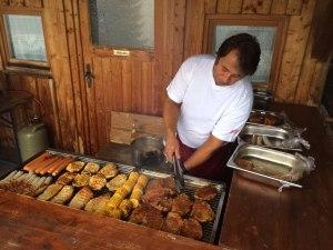 Steaks, Würstle und Maiskolben werden gegrillt