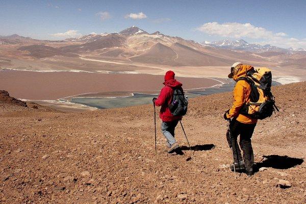 Zwei Wanderer in der Atacamawüste mit Gebirge